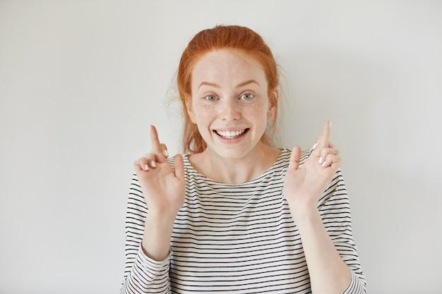 Headshot van bijgelovig roodharige meisje houdt haar vingers gekruist, doet wensen en gelooft oprecht in haar succes of overwinning. mooie jonge vrouw met sproeten in de hoop dat haar dromen uitkomen