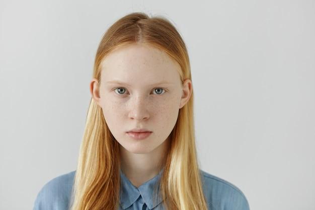 Headshot van blanke meisje met sproeten, blond haar en lichte ogen gekleed in blauwe school shirt staande tegen de witte muur
