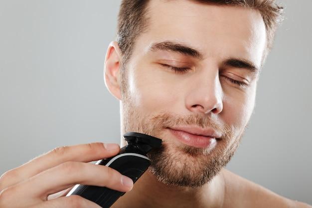 Headshot van blanke tevreden man 30s wordt uitgekleed in badkamer terwijl gezicht met snoeischaar over grijze muur scheert