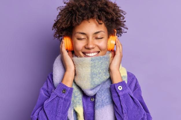 Headshot van blij krullend mooie jonge vrouw sluit ogen geniet van favoriete melodie houdt handen op draadloze koptelefoon draagt sjaal paars jasje.