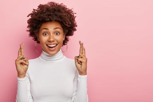 Headshot van blij lachende krullende vrouw kruist vingers met positieve uitdrukking, gelooft in geluk en succes, ziet er hopelijk recht uit, geïsoleerd over roze muur met lege ruimte opzij
