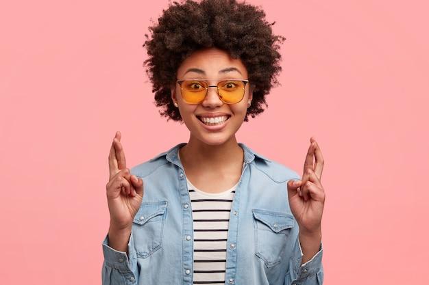 Headshot van blije jonge afro-amerikaanse vrouw gretig dromen uitkomen, kruist vingers voor het doen van wensen, draagt trendy tinten, glimlacht breed, toont perfecte tanden, modellen tegen roze muur.