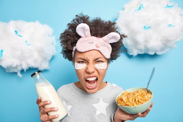 Headshot van boze vrouw schreeuwt luid houdt mond open houdt kom met ontbijtgranen en fles melk heeft ontbijt heeft een humeur wordt wakker vroeg in de ochtend geïsoleerd op blauwe muur
