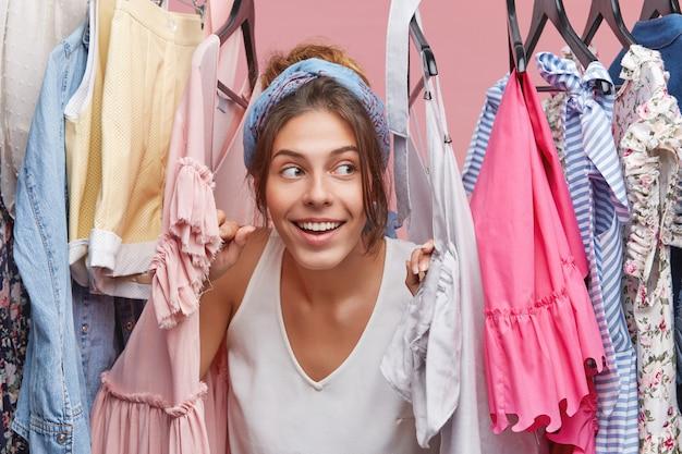 Headshot van charmante speelse jonge europese vrouw die verstoppertje speelt met broertje, zich verschuilend tussen de vele kleren die op het rek in haar kledingkast hangen. winkelen en consumentisme concept