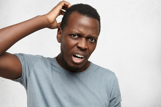 Headshot van clueless perplex jonge afro-amerikaanse man in grijs t-shirt op zoek met verwarde en verwarde uitdrukking, krabben hoofd