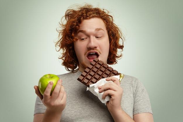 Headshot van dik mannetje met gemberhaar met grote reep chocola in de ene hand en groene appel in de andere, en kiest voor junkfood boven gezond vers fruit, klaar om een hapje te eten. mensen en obesitas