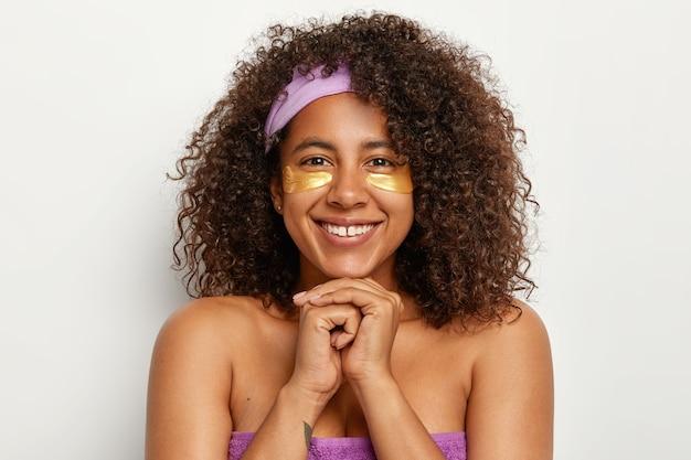 Headshot van een aangenaam uitziende dame met brede glimlach, afro-borstelig haar, staat halfnaakt, houdt de handen bij elkaar onder de kin, brengt gele vlekken onder de ogen aan voor huidherstel