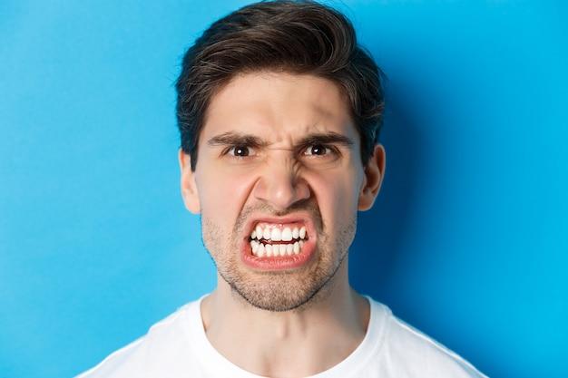 Headshot van een boze blanke man die met minachting en ontzetting kijkt, boos is op persoon, staande tegen een blauwe achtergrond