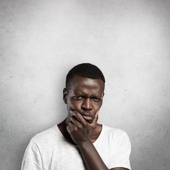 Headshot van een ernstige verbaasde afrikaanse man die zijn kin aanraakt, nadenkend en sceptisch kijkt over iets, diep in gedachten, aarzelend om een beslissing te nemen, fronsend.