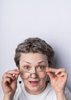 Headshot van een grijze haren vrouw met een bril met speelse uitdrukking op haar gezicht