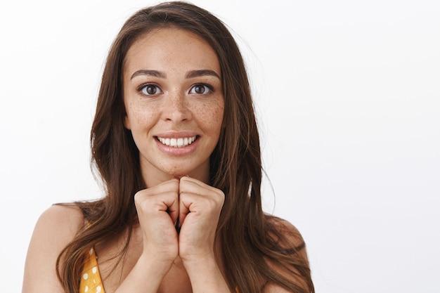 Headshot van een hoopvol, dom schattig jong meisje dat droomt om winnaar te worden, de handen in elkaar te klemmen en te smeken, vreugdevol te glimlachen, wensdroom die uitkomt, anticiperend op een groot moment