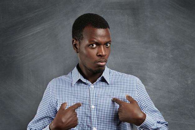 Headshot van een jonge donkere man die naar zichzelf wijst, excuses verzint of verbaal verdedigt, met een perplex en verbaasd uiterlijk alsof hij zegt: wie ik? uitdrukkingen, emoties en gevoelens van menselijke gezichten