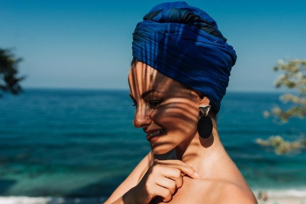 Headshot van een mooie glimlachende vrouw door de zee. zomervakantie concept.