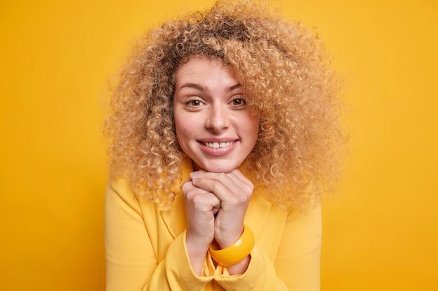 Headshot van een mooie vrouw met krullend haar houdt de handen onder de kin en glimlacht zachtjes terwijl ze in een goed humeur is