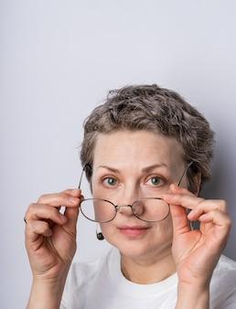 Headshot van een openhartige ogende grijze haren vrouw met een bril
