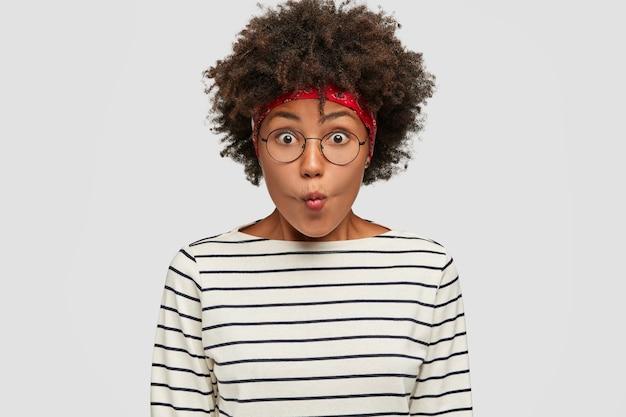 Headshot van een prachtig donkerhuidig meisje pruilt lippen en staart met een verbaasde blik, drukt ongeloof uit, draagt een hoofdband