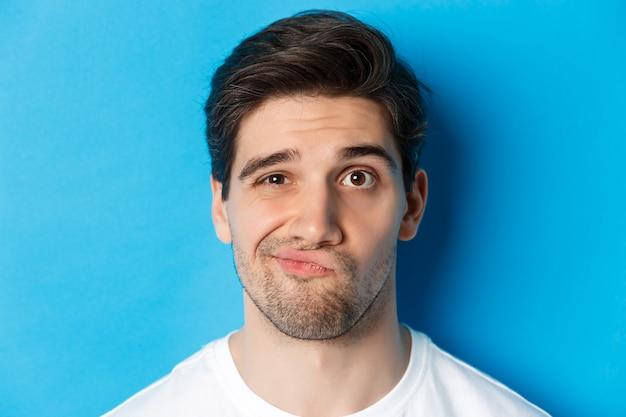 Headshot van een sceptische man die naar iets onamusant kijkt, grimassen trekt en aarzelend staat tegen een blauwe achtergrond.