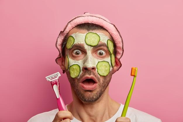 Headshot van emotioneel geschokte man heeft afgeluisterd in de ogen en mond geopend, plakjes komkommer op het gezicht aangebracht, kan ergens niet in geloven