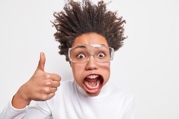 Headshot van emotionele donkere vrouw schreeuwt luid houdt mond open maakt uitstekend gebaar houdt duim omhoog draagt transparante bril witte coltrui poseert binnen. wauw ik vind het echt leuk
