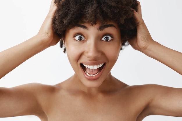 Headshot van emotionele en gelukkige dolgelukkig donkere vrouw poseren naakt schreeuwen van vreugde en opwinding hand in hand op krullend haar en vreugdevol starend