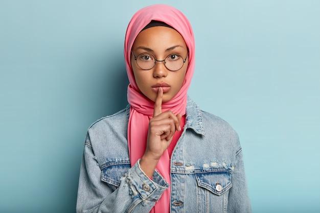 Headshot van ernstige vrouw in roze sjaal, denim jas, houdt de vinger over de lippen, vraagt geen geluid te maken, maakt een stil gebaar, heeft islamitische gelooft, draagt een ronde optische bril