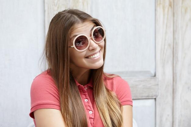 Headshot van flirterige jonge vrouw die modieuze tinten draagt met een speelse look en een schattige verlegen glimlach terwijl ze tegen een houten muur poseren met kopie ruimte voor uw informatie of advertentie