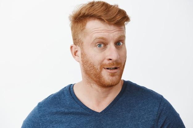 Headshot van geïntrigeerde knappe roodharige man met borstelharen in blauw t-shirt die zich omdraait met een onder de indruk en nieuwsgierige uitdrukking, aandachtig luisterend naar interessant verhaal over grijze muur