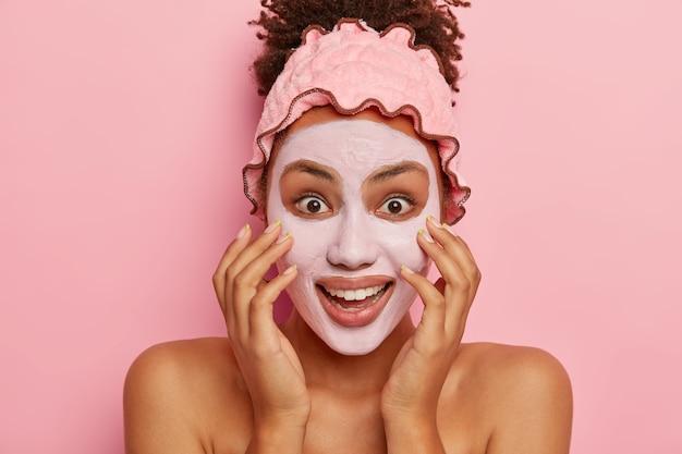 Headshot van gelukkige donkere vrouw past kleimasker toe, vermindert de zichtbaarheid van poriën, geniet van een effectief resultaat van schoonheidsproducten die diep in de huid doordringen, staat binnen op roze muur en toont blote schouders