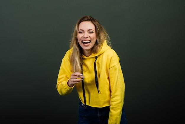 Headshot van gelukkige emotionele vrouw die uit de grond van haar hart lacht