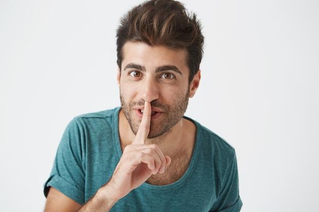 Headshot van gelukkige ongeschoren glimlachende spaanse man in vrijetijdskleding, wijsvinger vasthoudend aan lippen, en zijn vriendin vragen om stil te zijn nadat ze extra enthousiast is geworden voor een verjaardagscadeau.