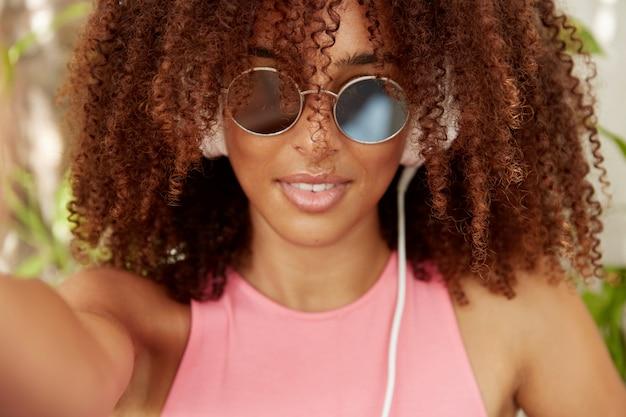 Headshot van gemengd ras zwarte jonge vrouw in trendy tinten, selfie maakt, trendy zonnebril draagt, heeft donkere pure gezonde huid. hipster meisje terloops gekleed, geniet van goede rust en amusement