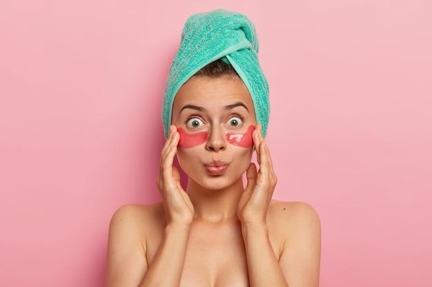 Headshot van geschokte blote schouders vrouw heeft natuurlijke schoonheid, vermindert rimpels onder de ogen, brengt collageenpleisters aan, heeft handdoek om hoofd gewikkeld