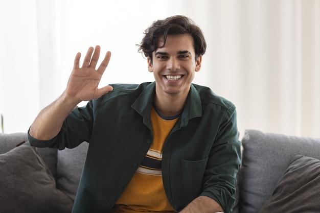 Headshot van glimlachende blanke man die naar de camera kijkt en hallo zwaait, videogesprek met vriend of vriendin, technologieconcept