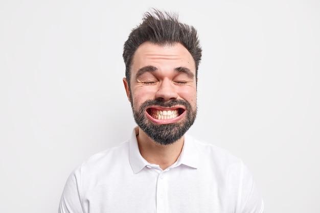 Headshot van grappige bebaarde volwassen europese man klemt tanden op elkaar draagt shirt sluit ogen maakt grappige grimas gekleed in shirt