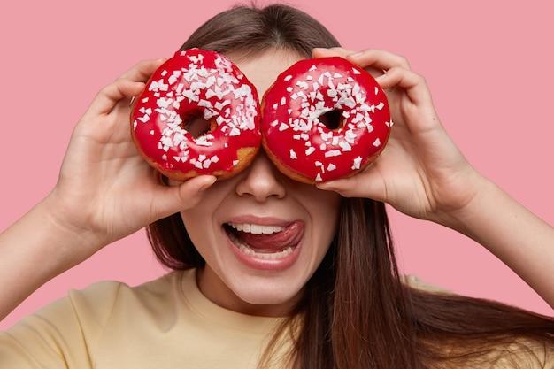 Headshot van grappige jonge europese vrouw bedekt ogen met twee geglazuurde donuts, likt lippen met tong, heeft donker haar