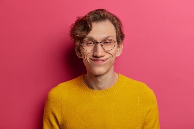 Headshot van grappige positieve hipster-man lacht vrolijk, heeft oprechte optimistische blik, draagt een ronde transparante bril en een gele trui, luistert naar een hilarisch verhaal, geïsoleerd op een roze muur