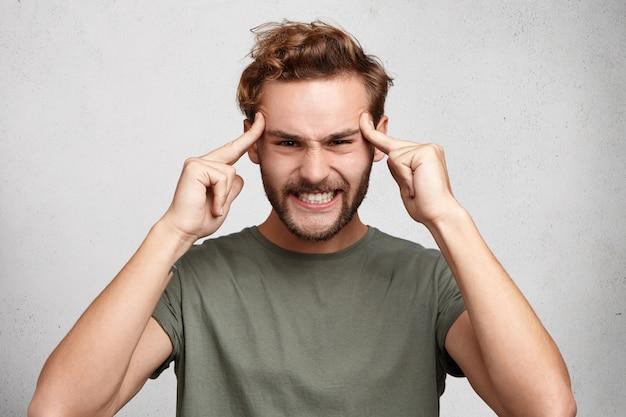 Headshot van jonge man houdt vingers op slapen, heeft een slecht geheugen, probeert zich te concentreren en te onthouden