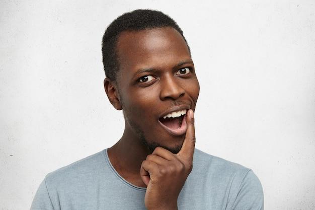 Headshot van knappe afrikaanse man terloops gekleed, uitroepend, vinger op zijn lippen houden