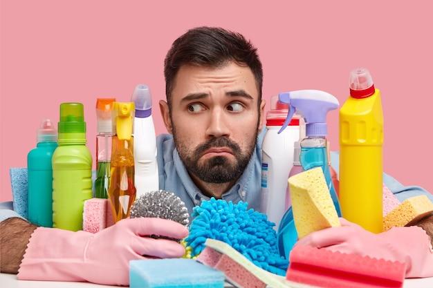 Headshot van knappe bebaarde man opzij gericht, heeft een verbaasde blik, omringd met schoonmaakmiddelen