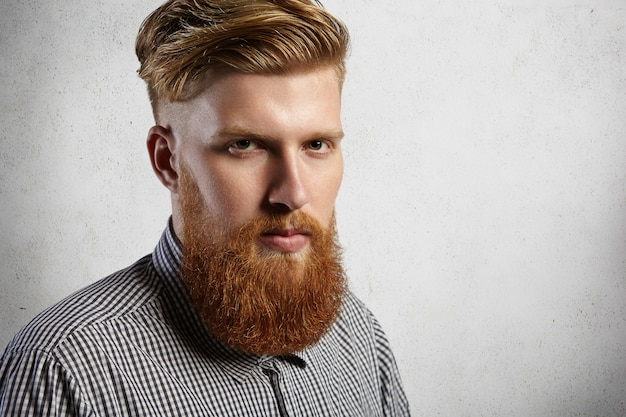 Headshot van knappe en stijlvolle blanke man gekleed in een geruit overhemd. brute en zelfverzekerde hipster met dikke baard en goed getrimde snorren.