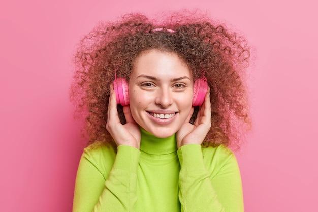 Headshot van knappe europese vrouw meloman met krullend kroeshaar draagt stereo koptelefoon luistert audio track heeft vrolijke stemming gekleed in casual coltrui geïsoleerd over roze muur.