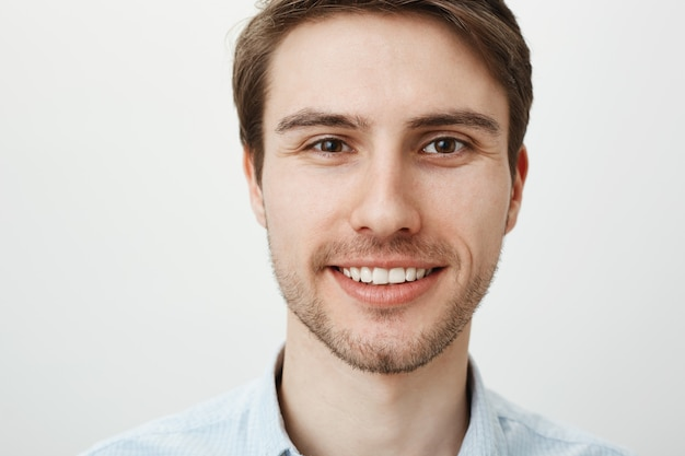 Headshot van knappe gelukkig lachende man die hoopvol kijkt
