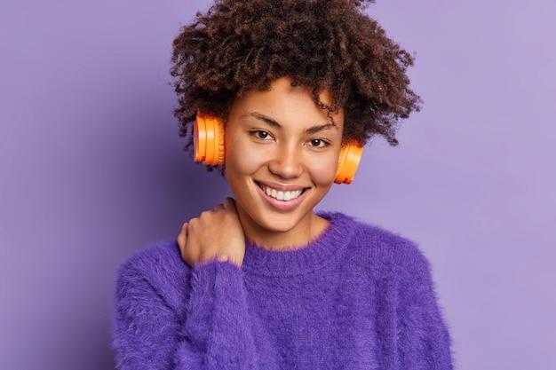 Headshot van knappe krullende harige vrouw met afro haar glimlach zachtjes raakt nek kijkt positief naar camera luistert audiotrack via draadloze stereo hoofdtelefoon