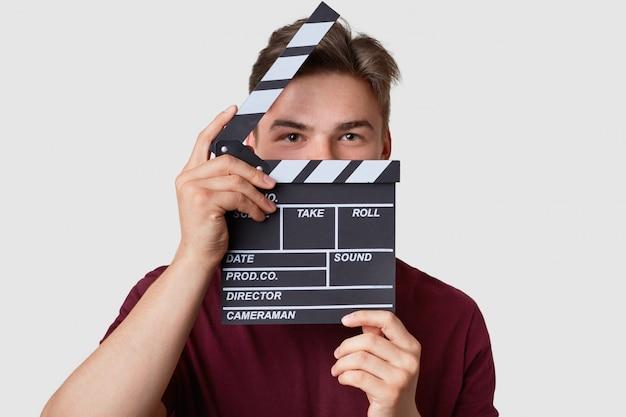 Headshot van knappe man verbergt gezicht met klepel bord