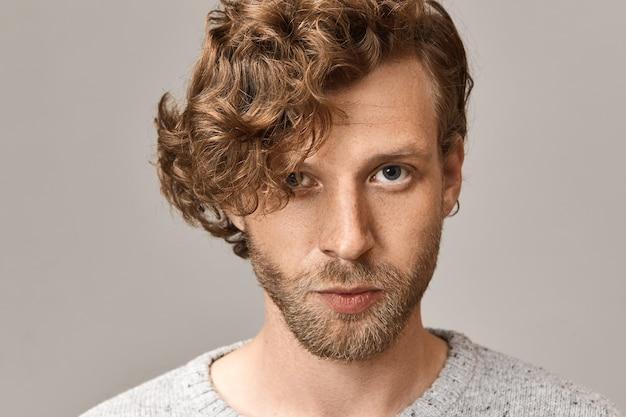 Headshot van knappe modieuze jongeman met blauwe ogen met stijlvolle gemberkrullen, sproeten en bijgesneden baard met zelfverzekerde gezichtsuitdrukking, grijze trui en ronde oorbel dragen