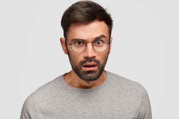 Headshot van knappe ongeschoren man reageert op iets met een ontevreden blik, heeft een verbaasde uitdrukking, staart, gekleed in vrijetijdskleding, geïsoleerd over een witte muur. emoties concept