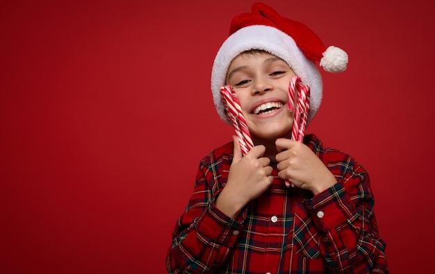 Headshot van knappe tedere kleine jongen, schattig lachend kind in kerstmuts en geruit hemd knuffelt zachtjes kerst lolly's zoete gestreepte zuurstokken, geïsoleerd op rode achtergrond, kopieer ruimte voor advertentie