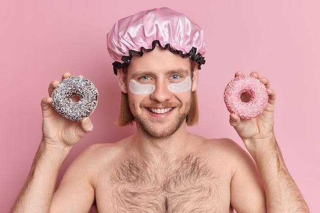 Headshot van lachende blije knappe man met stoppels en snor ondergaat schoonheidsprocedures na het nemen van een douche