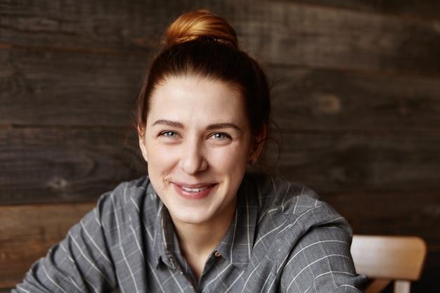 Headshot van leuk emotioneel kaukasisch meisje met haarknoop die rust in koffie heeft