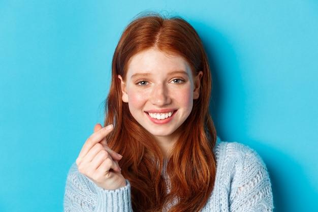 Headshot van leuke kaukasische vrouw met rood haar en sproeten die hartteken tonen en glimlachen, die zich tegen blauwe achtergrond bevinden.